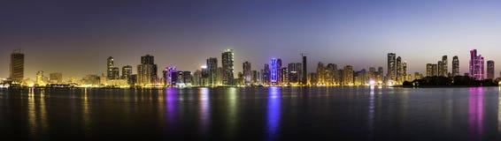 Panoramautsikt av Sharjah strandcityscape i UAE på skymning royaltyfri foto