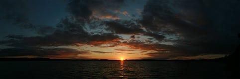 Panoramautsikt av solnedgången över sjön Arkivbilder