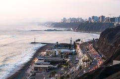 Panoramautsikt av solnedgången på den gröna kusten i Lima, Peru arkivfoton