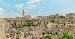 Panoramautsikt av typiska stenar Sassi di Matera och kyrkan av Matera under blå himmel med moln, effekt för tidschackningsperiod,