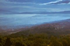 Panoramautsikt från en kulle i aftonen med låga moln över dalen royaltyfri foto