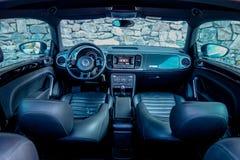 Panoramautsikt inom cockpiten för kupésportbil, modern instrumentbräda, läderplatser, kromprydnader, framsäten Arkivfoton