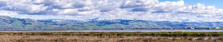 Panoramautsikt in mot gröna kullar och snöig berg på en kall vinterdag som tas från kusterna av ett träsk i södra San royaltyfri fotografi