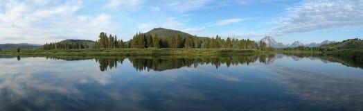Panoramautsikt: Snake River som reflekterar Rocky Mountains och himlen Royaltyfria Bilder