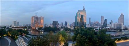 Panoramautsikten av aftonen Bangkok, solnedgång reflekterade i fönstren av skyskrapor längs Chao Phraya River arkivbilder