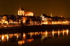 Panoramautsikten av den gamla staden av Torun på natten reflekterade med många Royaltyfria Bilder