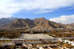 Panoramautsikten av den Lhasa staden som är främsta av Potala slott- och slottfyrkant, med moderna byggnad och berg, långt borta  Royaltyfria Bilder