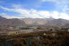 Panoramautsikten av den Lhasa staden som är främsta av Potala slott- och slottfyrkant, med moderna byggnad och berg, långt borta  Fotografering för Bildbyråer