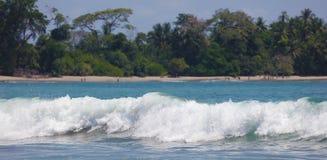 Panoramautsikten av den Manuel Antonio nationalparkstranden i Costa Rica, mest härlig stränder i världen, surfare sätter på land  fotografering för bildbyråer