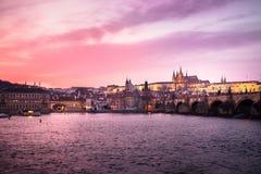 Panoramautsikten av den Prague slotten, Charles Bridge och St Vitus Cathedral reflekterade i den Vltava floden på skymning Arkivbilder