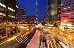 Panoramautsikten av ett gatahörn i den i stadens centrum Taipei staden med upptagen trafik skuggar på rusningstiden Royaltyfri Foto