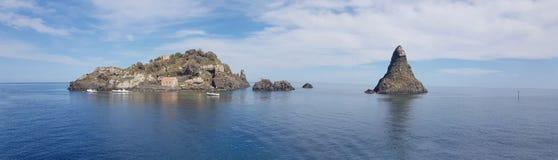 Panoramautsikten för Aci Trezza av den cyclopean kustlinjen som är berömd vaggar och ön i det blåa havet och himmel av Sicilien royaltyfria foton