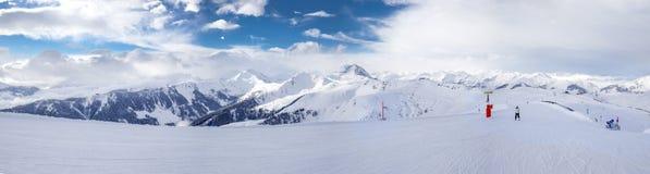 Panoramaview som skidar lutningar och skidåkare som skidar i det Kitzbuehel berget, skidar semesterorten med en bakgrund till fjä Royaltyfri Foto