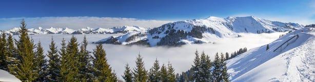 Panoramaview som skidar lutningar och skidåkare som skidar i det Kitzbuehel berget, skidar semesterorten med en bakgrundssikt til Royaltyfria Foton