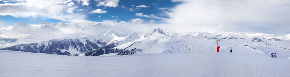 Panoramaview to ski slopes and skiers skiing in Kitzbuehel mountain ski resort with a background to Alps in Austria Royalty Free Stock Photo