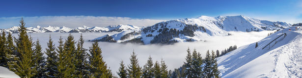 Panoramaview to ski slopes and skiers skiing in Kitzbuehel mountain ski resort with a background view to Alps in Austria Royalty Free Stock Photos