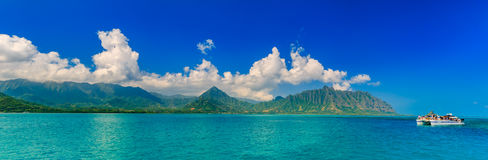 Panoramia of tropical lagoon, lush mountains, a catamaran and th. Panoramic view of a tropical lagoon, lush mountains and a catamaran in contrast with the ocean Royalty Free Stock Photos