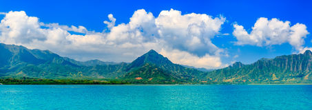 Panoramia of tropical lagoon and lush mountains and the ocean in. Panoramic view of a tropical lagoon and lush mountains in contrast with the ocean in Oahu Stock Image