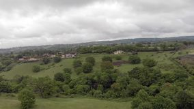 Panoramic aerial shot of the countryside with green hills, meadows and forests