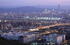 Panoramic aerial view of busy Taipei city. Keelung River, Dazhi Bridge, Songshan Airport and downtown area at dusk ~ A romantic evening in Taipei, Taiwan, with Royalty Free Stock Images