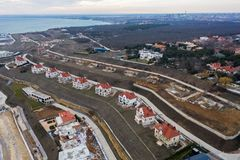 Panoramic aerial view of the cottage settlement by sea. Top view of the marine cottage village, line of strengthening the coast in. Zone of landslide. Villa on royalty free stock photography