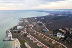 Panoramic aerial view of the cottage settlement by sea. Top view of the marine cottage village, line of strengthening the coast in. Zone of landslide. Villa on royalty free stock image