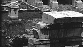 Archival Roman Forum in Rome. The panoramic aerial view of the Settimio Severo arch and Column of Foca. Roman Forum in Rome city. BW historical archival of Rome stock video footage