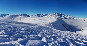 Panoramic Alpes snow view. A panoramic view on Alpes snow mountains from one of the tops over clouds, with many ski tracks on snow. Alpes, France, Europe Stock Images