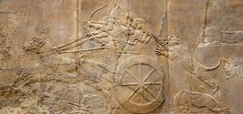 Panoramic Assyrian wall relief. Assyrian wall relief of the royal lion hunt. Ancient carving panoramic panel from Middle East history. Remains of the culture of stock photo