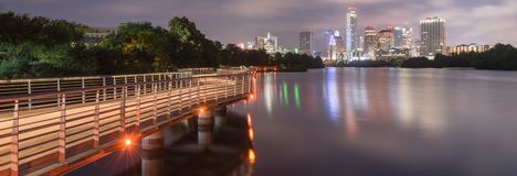 Panoramic Austin downtown skyscraper reflection along Colorado R. Panorama view beautiful downtown Austin, America from boardwalk along Colorado River. Long stock images