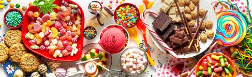 Panoramic banner with an assorted colorful candy. Chocolate, cookies and ice cream for a kids birthday party in a full frame background view royalty free stock photography