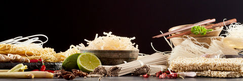Panoramic banner with assortment of Asian noodles. Panoramic banner with large assortment of dried Asian noodles, seasoning ingredients and chopsticks over a Stock Image