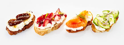Panoramic banner with four assorted canapes royalty free stock photo
