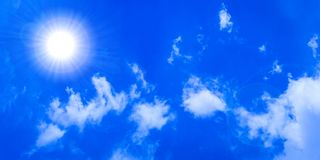 Glowing Sun in Blue Sky. A panoramic banner with the glowing sun, flares and white clouds in the blue sky royalty free stock photo