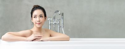 Panoramic banner image of young beautiful Asian lady relaxing and looking away while sitting in the bathtube.Spa treatments for. Beauty and health with skin stock photos