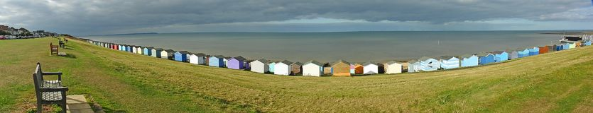 Panoramic beach huts sea view stock images