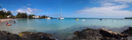 Panoramic beach view in Mauritius. Extra wide true panoramic view of Pereybere beach in exotic Mauritius with tourist leaving coast in a boat to go at sea Stock Image