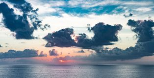 Panoramic beautiful view on sunset over the ocean. ?olorful cloudy sky and setting sun. Stunning cloudy sky panoramic view royalty free stock photography