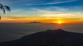 Panoramic beautiful view from top of the volcano Agung at dawn. View of the rising sun and Rinjani mount on the horizon royalty free stock photo