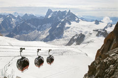 The Panoramic cable car at Aiguille du Midi. CHAMONIX, FRANCE - JULY 23, 2015: The Panoramic cable car at Aiguille du Midi against 'White valley Royalty Free Stock Photos