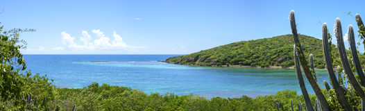 Panoramic Caribbean island paradise. Beautiful wide panoramic of Melena Bay and Soldier Point with blue and turquoise sea bordered by dense green vegetation on Royalty Free Stock Photo