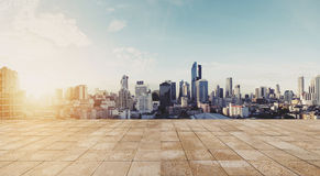 Panoramic city view in sunrise with empty wooden floor Royalty Free Stock Photography
