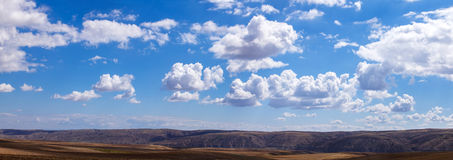 Panoramic clouds over hills. And fields Royalty Free Stock Images