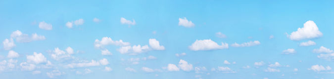 Panoramic cloudscape with white cumulus against blue sky Royalty Free Stock Photo