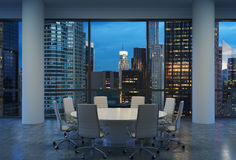 Panoramic conference room in modern office, cityscape of New York skyscrapers at night, Manhattan. Royalty Free Stock Photography