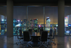 Panoramic conference room in modern office, cityscape of Singapore skyscrapers at night. Black chairs and a black round table.