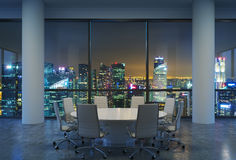 Panoramic conference room in modern office, cityscape of Singapore skyscrapers at night. White chairs and a white round table. Stock Photo