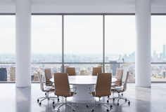 Panoramic conference room in modern office, New York city view. Brown chairs and a white round table. Royalty Free Stock Photography