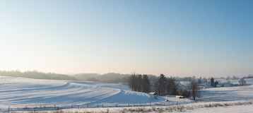 Panoramic country background farmland in Appalachia in snow. Panoramic country background of snow-covered farmland and barn and silos at sunrise in rural royalty free stock image