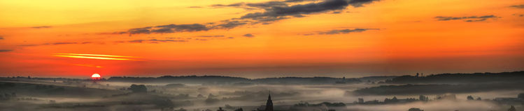 Panoramic countryside sunset. Scenic panoramic view of orange sunset and cloudscape over rural village shrouded in mist Royalty Free Stock Photography